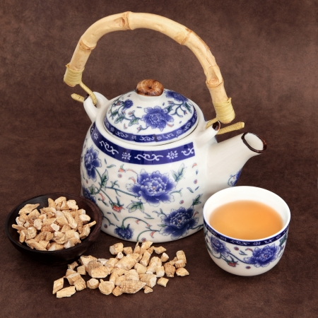 Ginseng herb tea with chinese teapot and cup over brown lokta handmade paper  Stock Photo