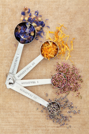 Herbal medicine with lavender, cornflower, heather and marigold dried flowers in measuring spoons also used in witch magical potions. photo