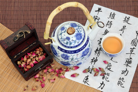 oriental medicine: Rose flower buds with oriental style tea pot and cup, and calligraphic script over bamboo