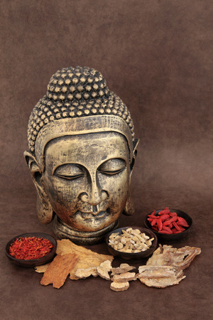 holistic therapy: Chinese herbal medicine selection with buddha head over handmade lokta paper background  Stock Photo