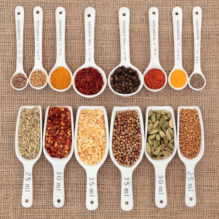 quantity: Herb and spice selection in metric measuring spoons and scoops over hessian