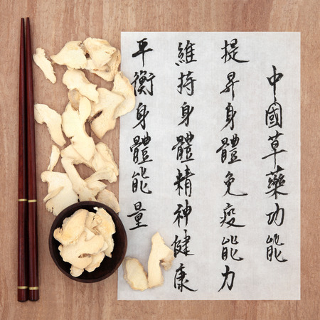 qi: Ginger root chinese herbal medicine with mandarin calligraphy script on rice paper describing the medicinal functions to maintain body and spirit health and balance energy  Stock Photo