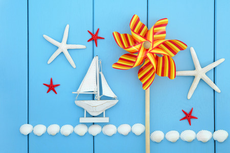 beach toys: Sea shell, toy windmill and decorative sailing boat abstract over wood background  Stock Photo