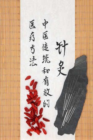 Acupuncture needles and mandarin script on rice paper over bamboo with wolfberry fruit  Translation describes acupuncture chinese medicine as a traditional and effective medical solution  photo