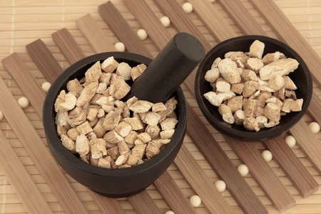 ginseng: Korean ginseng chinese herbal medicine in a mortar with pestle and bowl  Panaz schinsen  Ren shen