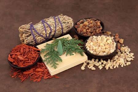Frankincense, myrrh, sandalwood, incense cones , cedar leaf and smudge stick over lokta paper background