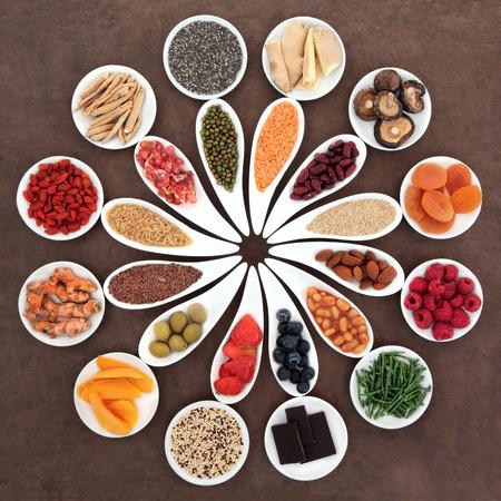 Healthy super food selection in white porcelain bowls over brown lokta paper background photo