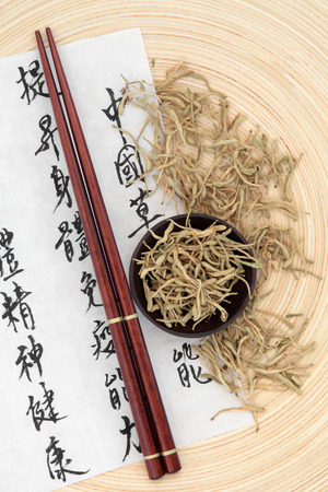 honeysuckle: Chinese herbal medicine of dried honeysuckle flowers with mandarin calligraphy script on rice paper describing the medicinal functions to maintain body and spirit health and balance body energy  Stock Photo