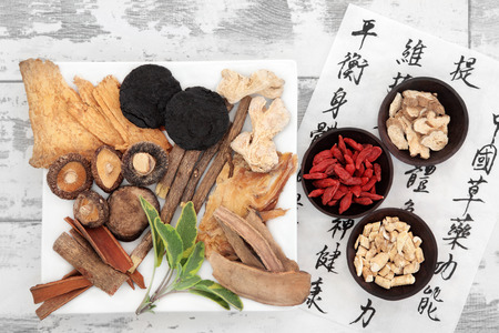 Chinese herbal medicine selection and mandarin calligraphy script on rice paper describing the medicinal functions to maintain body and spirit health and balance body energy