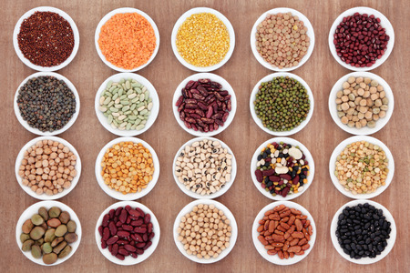 legumbres secas: Amplia selección pulsos secos en platos de porcelana blanca sobre fondo de papiro Foto de archivo