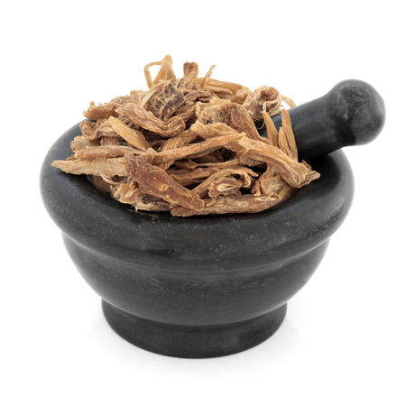 bu: Stemona root chinese herbal medicine in a black stone mortar with pestle over white background  Bai bu