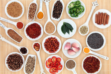 quantity: Herb and spice selection in white porcelain measuring spoons, scoops and bowls over bamboo  Stock Photo