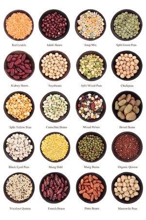 Amplia selección legumbres secas en cuencos de madera sobre el fondo blanco con títulos Foto de archivo