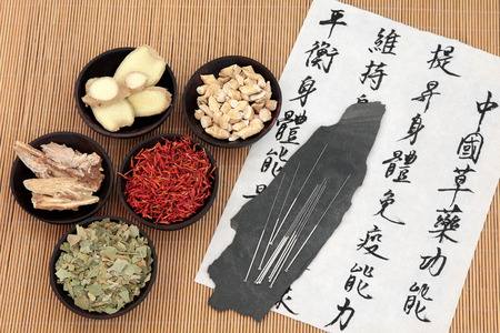 Chinese herbal medicine selection with acupuncture needles and mandarin calligraphy script on rice paper describing the medicinal functions to maintain body and spirit health and balance energy