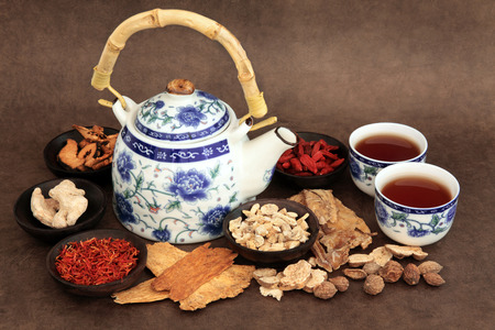 teas: Chinese herb tea selection with traditional teapot and cups over brown lokta handmade paper background  Stock Photo