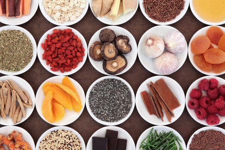 Healthy super food selection in porcelain bowls over brown lokta paper background  photo