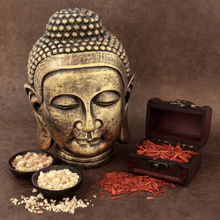 Frankincense: Gold buddha with incense of frankincense, myrrh and sandalwood over handmade lokta brown paper background