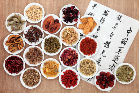 chinese medicine: Chinese herbal medicine selection with calligraphy script describing the medicinal functions to maintain body and spirit health and balance body energy  Stock Photo