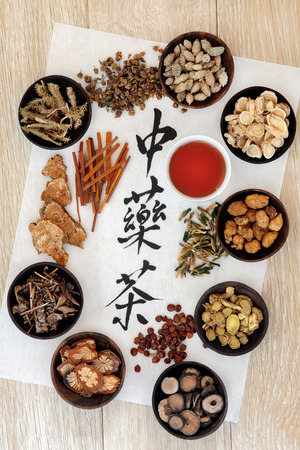 ginseng: Chinese herbal tea calligraphy script on rice paper with herb selection and cup over light oak wood