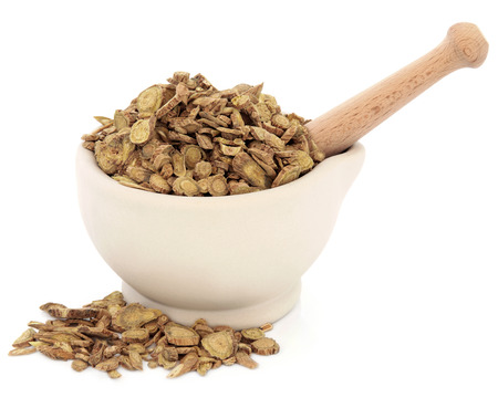 skullcap: Skullcap root chinese herbal medicine in a stone mortar with pestle over white background  Huang qin  Scutellaria  Stock Photo
