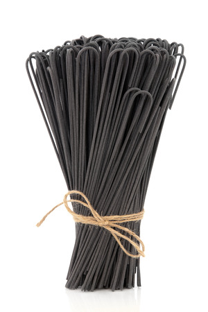 Cuttlefish ink spaghetti pasta tied in a bunch over white background  photo