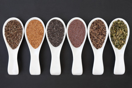 Seed food selection in porcelain scoops over slate background  photo