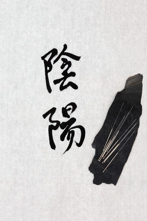 eastern health treatment: Acupuncture needles with yin and yang calligraphy symbol on rice paper  Translation reads as yin yang