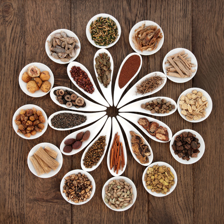 Large chinese herbal medicine selection in china bowls over old oak background