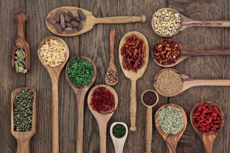 aniseed: Herb and spice selection in wooden spoons and scoops over oak wood background