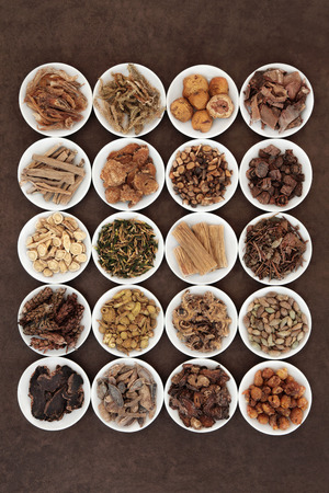 Large chinese herbal medicine selection in white china bowls over lokta paper background
