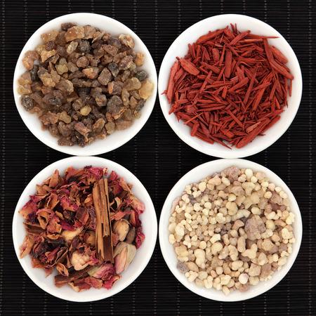 Frankincense, myrrh, sandalwood and fragrant rose pot pourri over bamboo background