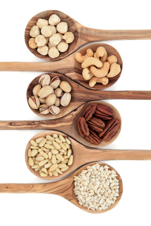 Nut varieties of hazelnut, cashew, pistachio, pecan, pine kernel and chopped almonds in olive wood spoons over white background  Top to bottom  photo