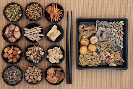 oriental medicine: Large chinese herbal medicine selection in wooden bowls and square dish with chopsticks over bamboo  Stock Photo