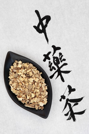 licorice: Licorice root with chinese herbal tea calligraphy script over rice paper  Translation reads as licorice root
