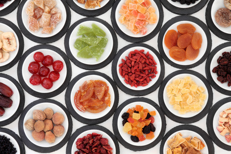 crystallized: Dried fruit selection in white bowls on slate rounds over white background