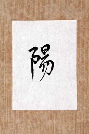 chinese script: Chinese yang symbol in mandarin calligraphy script on rice paper over brown paper background  Stock Photo
