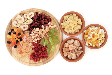 Dried fruit selection on a wooden board and in terracotta bowls over white background  photo