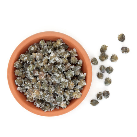 Salted capers in a terracotta bowl and loose over white background  photo