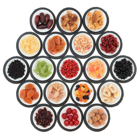 cherry varieties: Large dried fruit selection in white bowls on slate rounds over white background