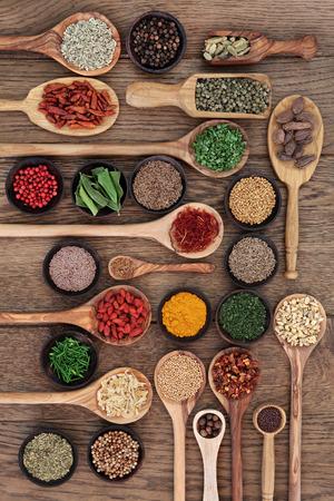 legumbres secas: Gran selección de especias y hierbas en cuencos de madera, cucharas y cucharones sobre fondo de madera de roble