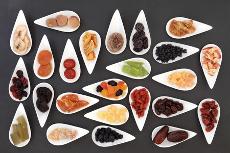 glace: Large dried fruit selection in white dishes over slate background  Stock Photo