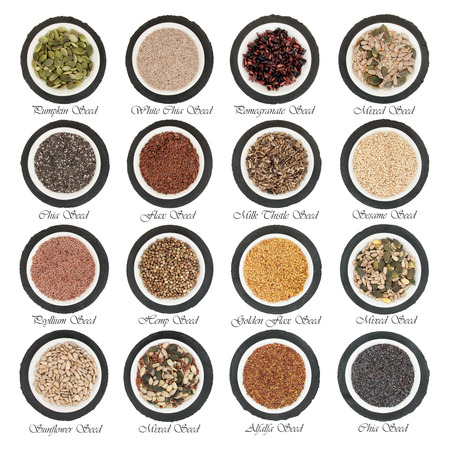 linseed: Large seed super food selection in  porcelain bowls over slate rounds and white isolated background with titles