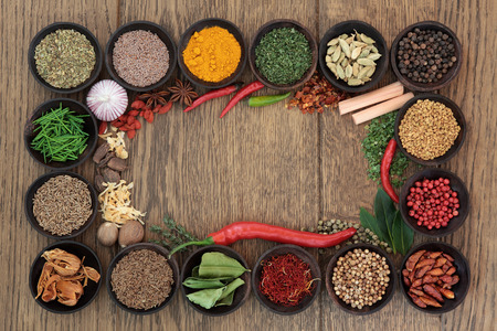 mace: Herb and spice selection forming an abstract background border over oak  Stock Photo