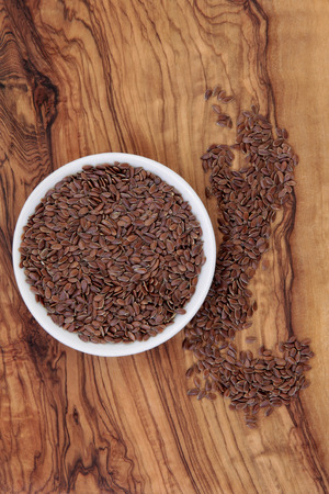 flax seeds: Linseed flax in a white porcelain bowl on an olive wood board