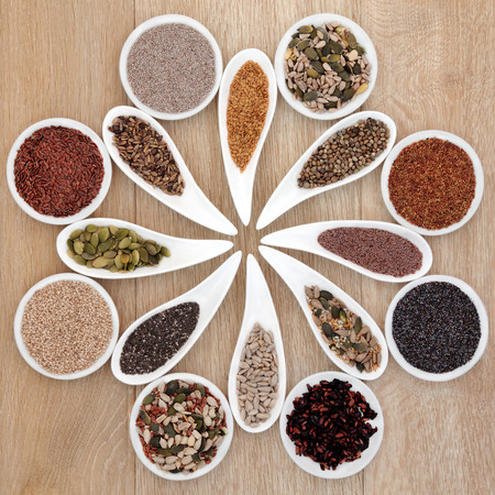 Large super food seed selection in porcelain bowls over light oak background  photo