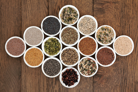 chia: Large seed superfood selection in white porcelain bowls over oak background