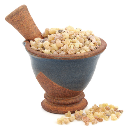 Frankincense: Frankincense in a mortar with pestle over white background