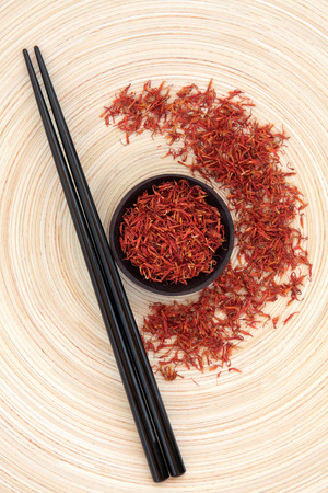 chinese herbal medicine: Safflower chinese herbal medicine with chopsticks on a circular wooden bowl  Hong hua
