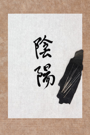 eastern health treatment: Acupuncture needles with yin and yang calligraphy symbol on rice paper  Stock Photo