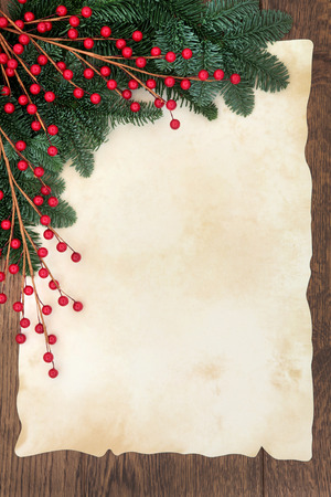 Christmas and winter background border with fir and red ball decorative sprays over old parchment paper and oak wood